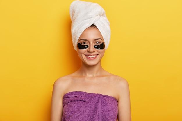 Glückliche europäische frau mit sanftem lächeln, hat schwarze kollagenflecken, reduziert das problem von dunklen ringen unter den augen, eingewickelt in handtuch auf kopf und über körper, verbessert hautzustand