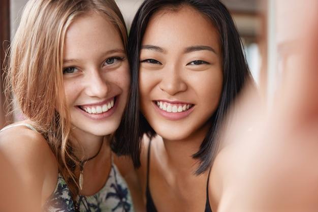 Glückliche europäische frau umarmt beste asiatische freundin, macht selfie, steht nahe beieinander.