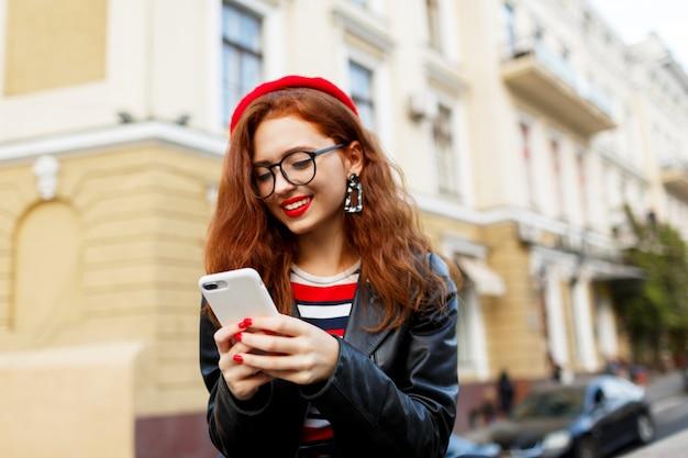 Glückliche fabelhafte ingwerfrau in der stilvollen roten baskenmütze in der straße unter verwendung des smartphones