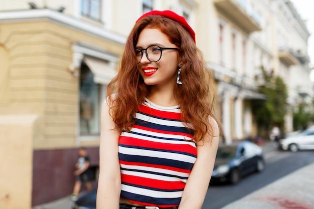 Glückliche fabelhafte ingwerfrau in der stilvollen roten baskenmütze in der straße