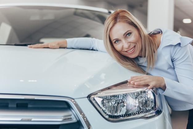 Glückliche fällige frau, die ihr neues automobil am verkaufsstellensalon umfaßt