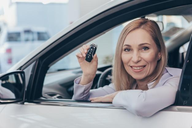 Glückliche fällige frau, die in ihrem neuen automobil hält autoschlüssel sitzt