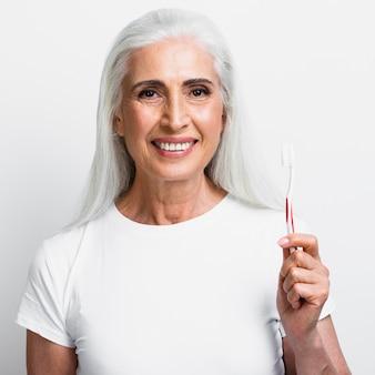 Glückliche fällige frau, die tootbrush anhält