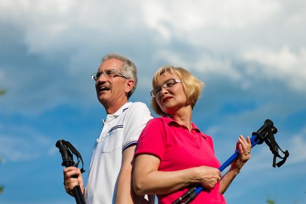 Glückliche fällige oder ältere paare, die das nordic walking im sommer tun