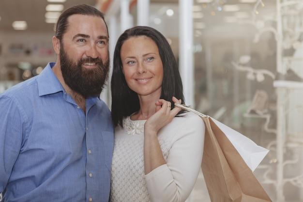 Glückliche fällige paare, die im einkaufszentrum kaufen