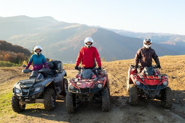 Glückliche fahrer in schutzhelmen, die bei sonnenuntergang extremes fahren auf atv-quad-motorrädern in den sommerbergen genießen.