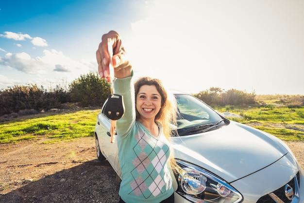 Glückliche fahrerin hält autoschlüssel in der nähe ihres neuen autos.