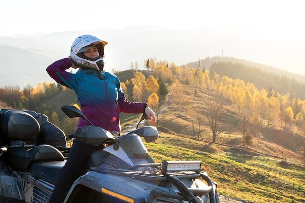 Glückliche fahrerin in schutzhelm, die bei sonnenuntergang offroad-fahren auf einem atv-quad-motorrad in den herbstbergen genießt.