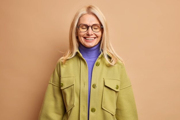 Glückliche faltige blonde frau schließt die augen, lächelt sanft und erinnert sich an etwas angenehmes, das positive emotionen ausdrückt.