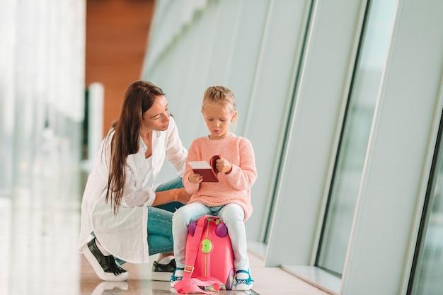 Glückliche familie am flughafen, der auf koffer mit der bordkarte wartet auf einstieg sitzt