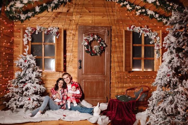 Glückliche familie am heiligabend, die zusammen nahe geschmücktem baum am wohnzimmer, zu hause sitzt. vater, mutter und baby.