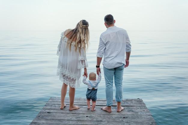 Glückliche familie am pier. rückansicht. mann und frau halten ihr kleinkindkind, das nahe dem see steht.