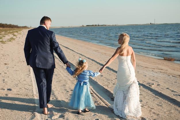 Glückliche familie am strand bei sonnenaufgang - kind, mutter und vater