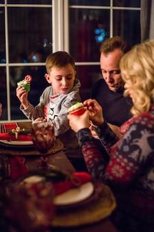 Glückliche familie am tisch am silvesterabend