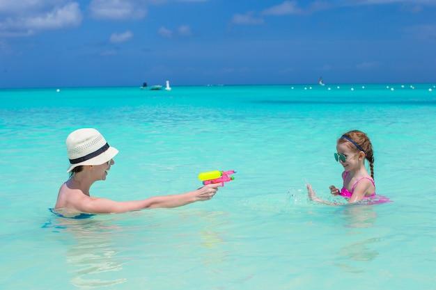 Glückliche familie am tropischen strand, der spaß hat