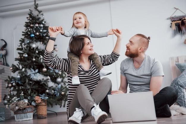 Glückliche familie am weihnachten in den morgenöffnungsgeschenken zusammen nahe dem tannenbaum. das von familienglück und wohlbefinden