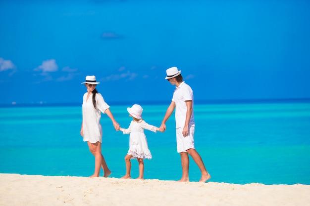Glückliche familie am weißen strand auf den malediven