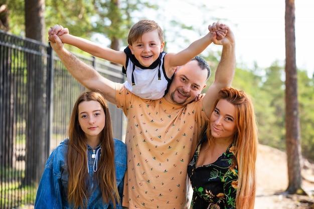 Glückliche familie auf dem aufstellen der natur gegen den des waldes