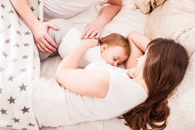 Glückliche familie auf dem bett. mutter und weiter schlafen mit ihrem kleinen mädchen. mama stillt ihre kleine tochter