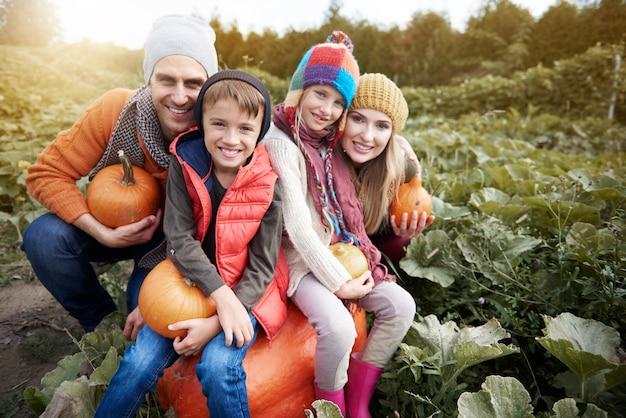 Glückliche familie auf dem feld voller kürbis