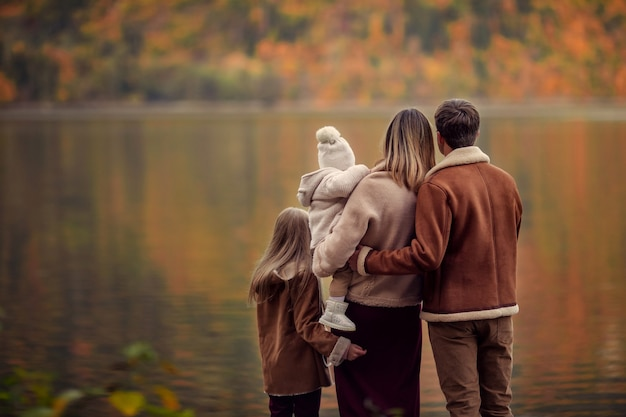 Glückliche familie auf dem see in den bergen für einen spaziergang im herbst