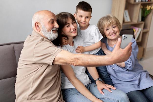 Glückliche familie auf der couch, die selfie nimmt