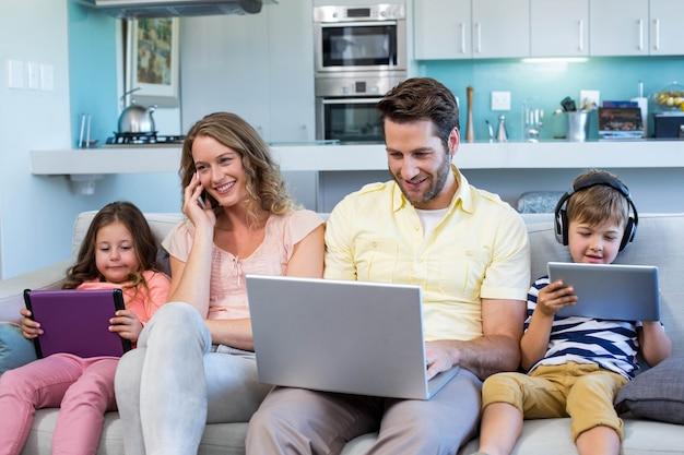 Glückliche familie auf der couch, die zusammen geräte verwendet
