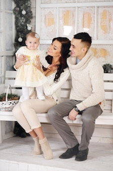 Glückliche familie auf der veranda mit weihnachtsdekorationen