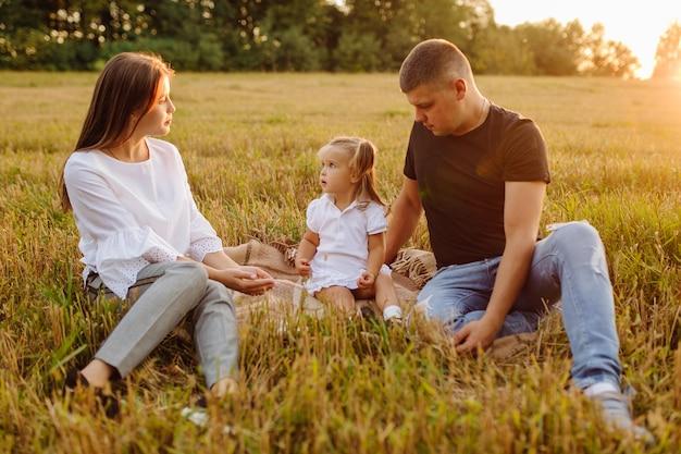 Glückliche familie auf einem feld im herbst. mutter, vater und baby spielen in der natur in den strahlen des sonnenuntergangs