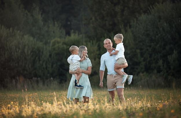 Glückliche familie auf einem feldspaziergang mit zwei kindern
