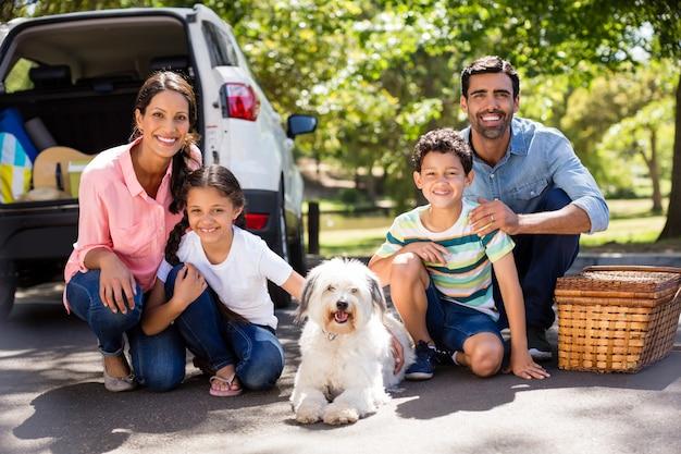 Glückliche familie auf einem picknick, das neben ihrem auto sitzt