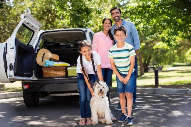 Glückliche familie auf einem picknick, das neben ihrem auto steht
