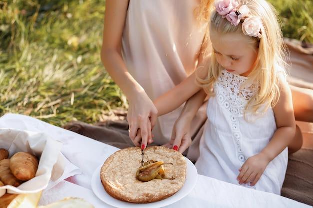 Glückliche familie auf einem sommerpicknick schneidet einen kuchen. nahansicht