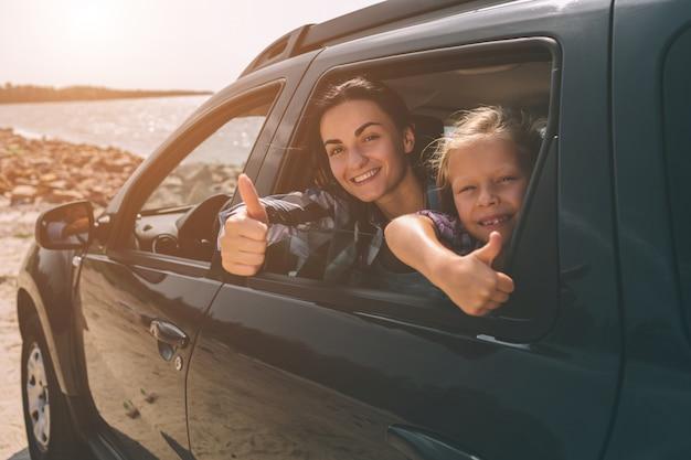 Glückliche familie auf einer autoreise in ihrem auto. vater, mutter und tochter reisen am meer, am meer oder am fluss entlang. sommerfahrt mit dem auto