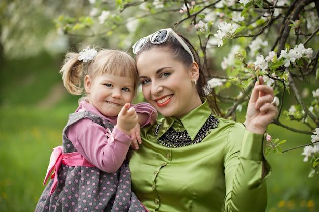 Glückliche familie auf mutter- und babytochter der natur draußen auf dem grünen garten