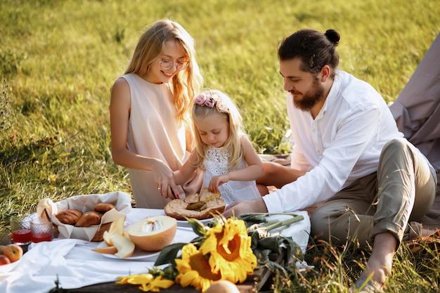 Glückliche familie auf sommerpicknick schneidet kuchen