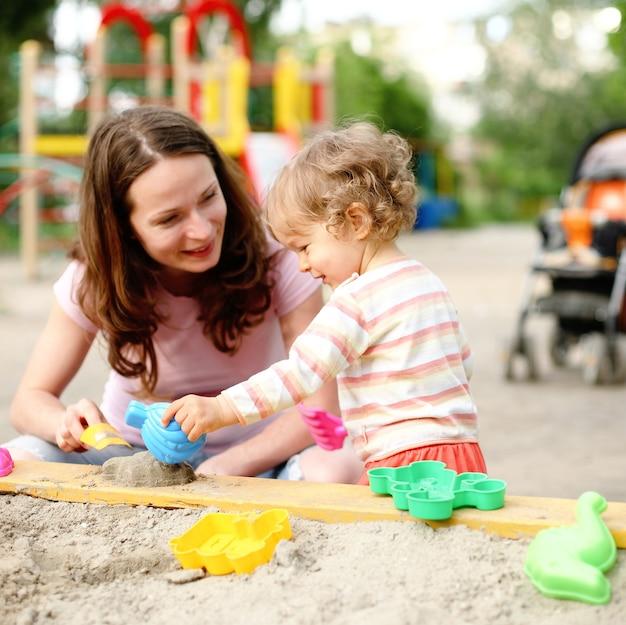 Glückliche familie auf spielplatz im sommer