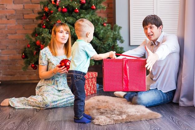 Glückliche familie, baby, das weihnachtsgeschenk hält