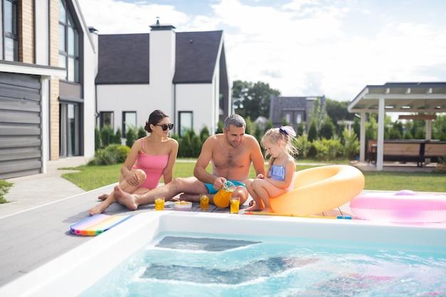 Glückliche familie beim chillen. glückliche familie, die sich an einem heißen sommertag entspannt am pool entspannt