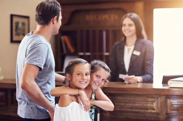 Glückliche familie beim einchecken im hotel an der rezeption