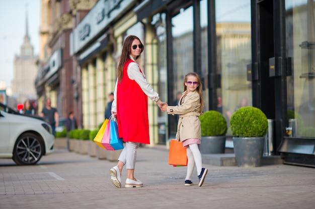 Glückliche familie beim einkaufen im freien. mutter und tochter kaufen beim einkaufen ein und haben spaß beim spazierengehen auf der straße im freien.