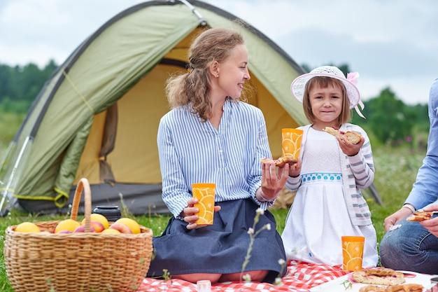 Glückliche familie beim picknick auf dem campingplatz. mutter und tochter essen in der nähe eines zeltes auf der wiese oder im park