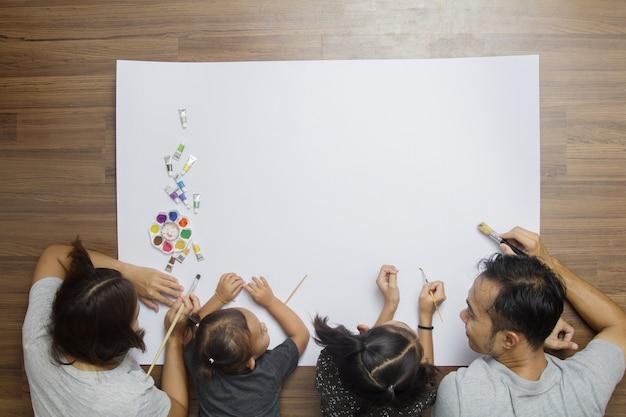 Glückliche familie der draufsicht, die auf boden mit der malerei unter verwendung der aquarelle liegt