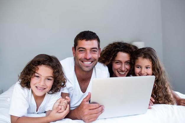 Glückliche familie der familie, die zusammen laptop auf bett verwendet