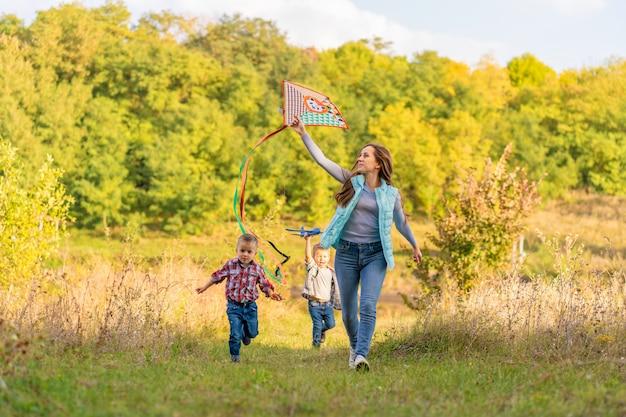Glückliche familie der jungen mutter und seiner kinder starten einen drachen auf natur bei sonnenuntergang. familienurlaub