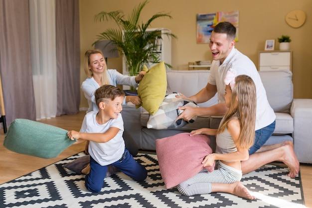 Glückliche familie der vorderansicht, die mit kissen spielt
