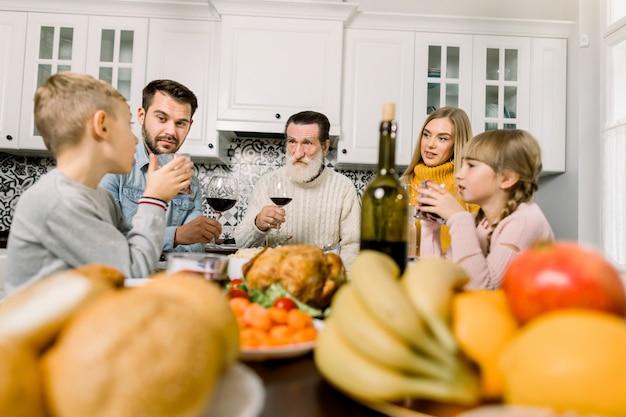 Glückliche familie des großvaters, der jungen eltern und des kinderjungen und -mädchens, die erntedankfest in der gemütlichen küche feiern