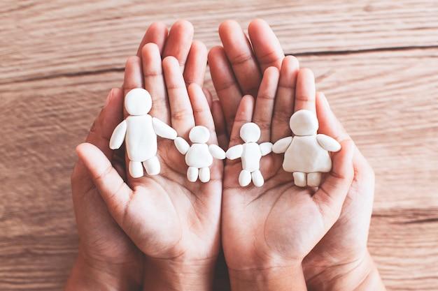 Glückliche familie des plastilintons auf kinder- und elternhänden. glückliches familien- und liebeskonzept.