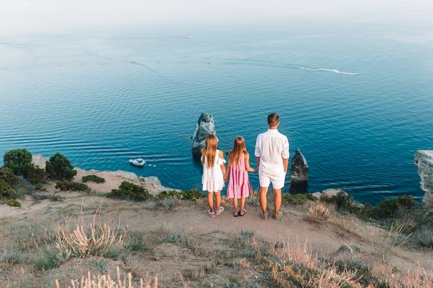 Glückliche familie des vaters und der kinder in den bergen am sonnenuntergang. reisetourismus abenteuer konzept