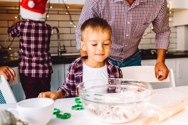Glückliche familie des vaters und zwei kinderzwillingsöhne backen vor weihnachten kekse in der küche.